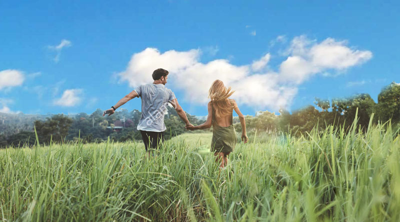 couple running in field with blue sky